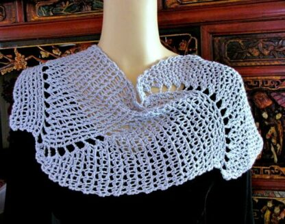 Capelet of lacy beaded slip stitches in a swirl pattern.