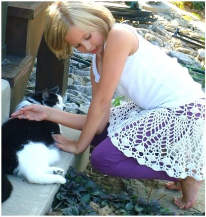 """Tween-aged girl wears an """"exploded doily"""" style skirt by Doris Chan as she pets a cat."""