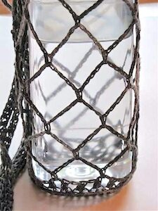 A water bottle carrier of a very open chain mesh, showing where the nearly invisible join of each round is, thanks to the tall stitch equivalent.