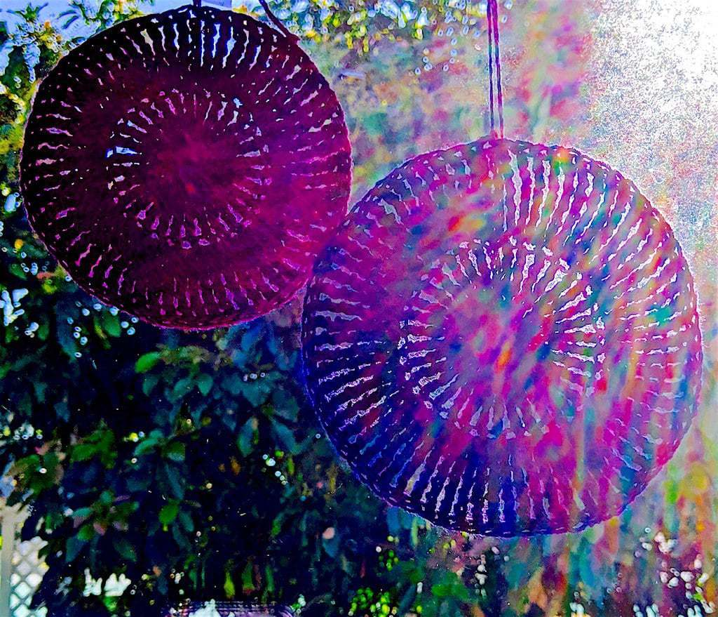 Tirple treble circle and Quadruple treble circle shown in a window with rainbow light filtered through them