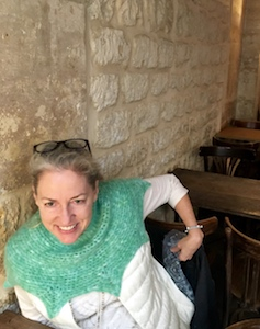"""Vashti wears her crocheted angora """"Orbit Halo"""" cowl in a stone-walled breakfast cafe in the old part of Paris"""