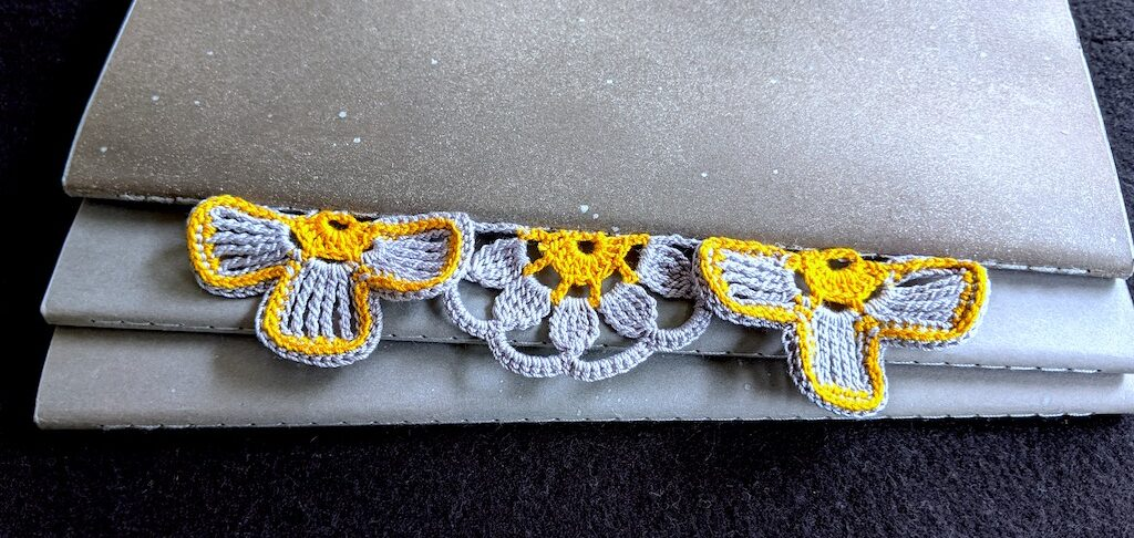 Three half-flowers in antique gold and silver colors attached to spine of large Molestine crochet notebook.