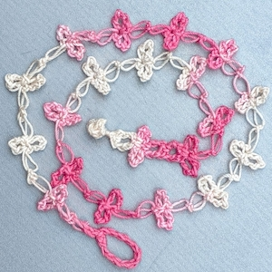 Crochet mask chain of lacy pink love knots and crocheted fasteners.
