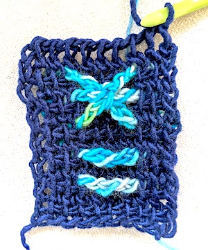 Ten-stitch rows with a solid dark color background of Tunisian extended simple stitch and variegated light blue raised horizontal bars over 4 stitches of the row, and at the top last rows, three of these bars are wrapped with a stitch in the middle to resemble a raised asterisk shape